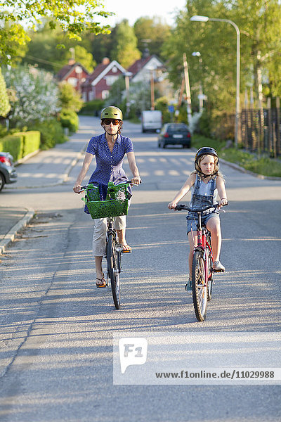 Mother and daughter cycling together
