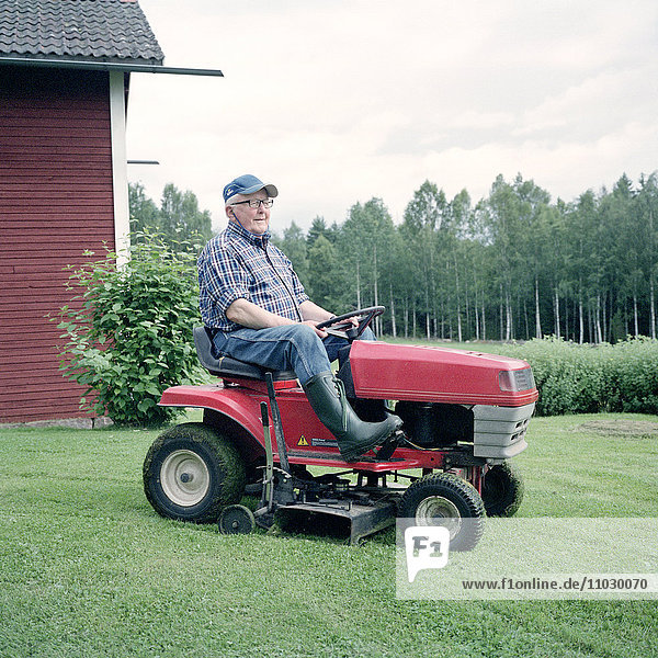 Senior man driving lawn mower
