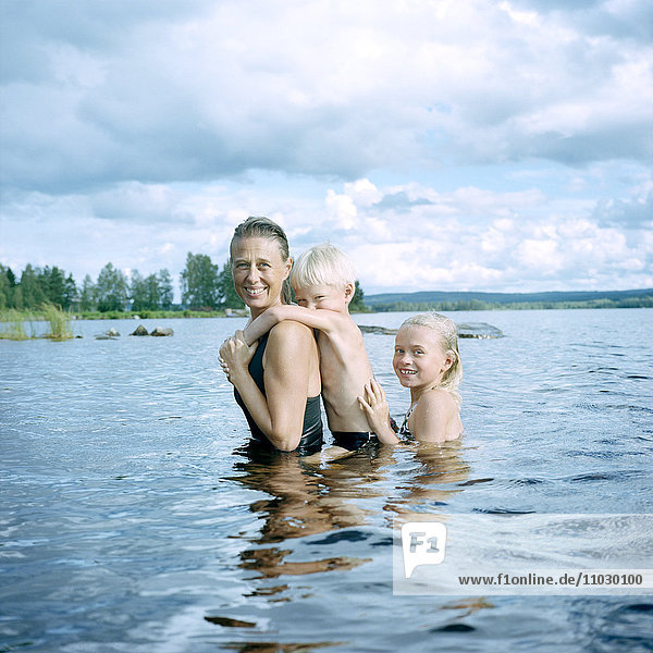 Mother with children swimming in lake