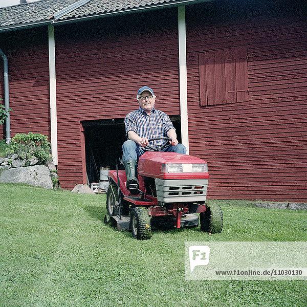 Senior man driving lawn mower