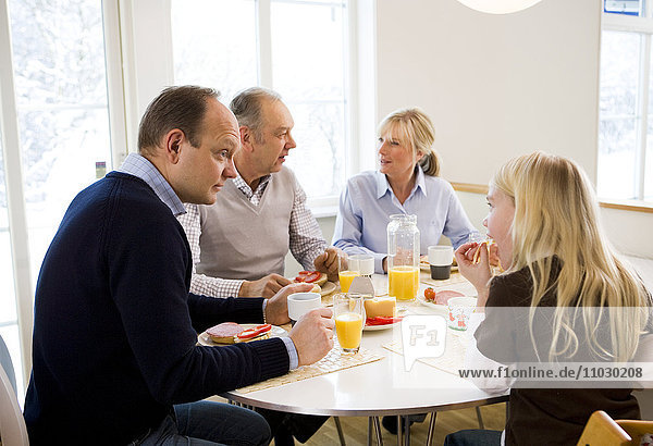 Family sitting around table eating breakfast