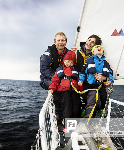Family sitting in sailing boat  smiling