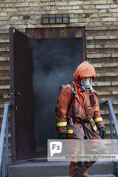 Firefighter going out from building full of smoke