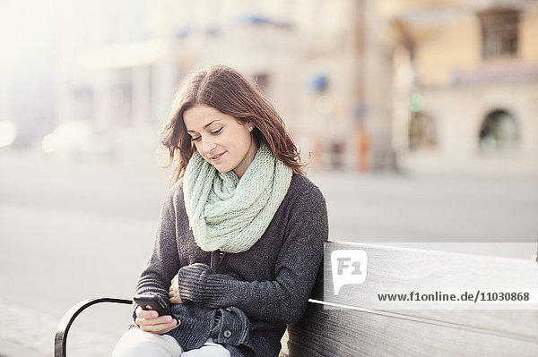 Young woman sitting on bench using phone