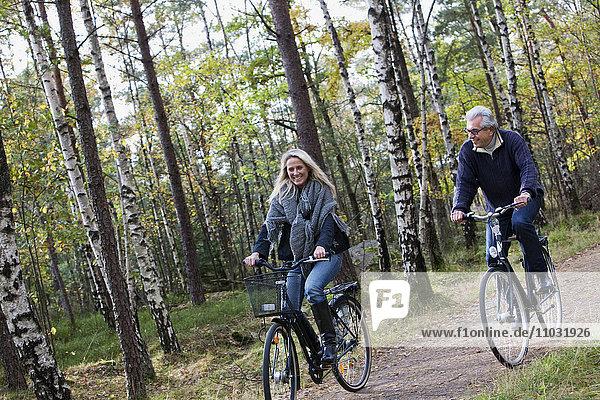 Senior couple cycling in forest  Delsjon  Gothenburg  Sweden
