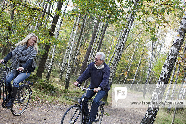 Senior couple cycling in forest  Delsjon  Gothenburg  Sweden