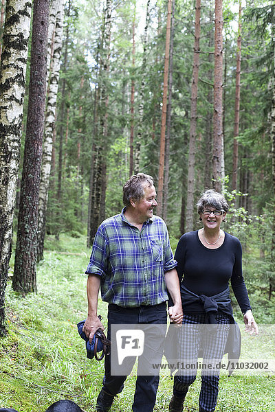 Mature couple walking through forest
