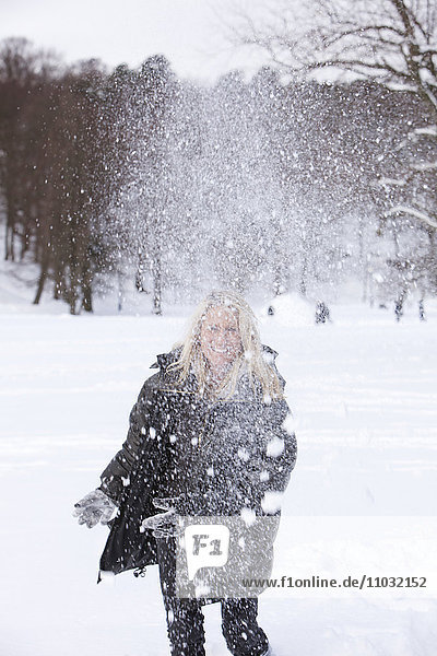 Mature woman throwing snowballs  Gothenburg  Sweden