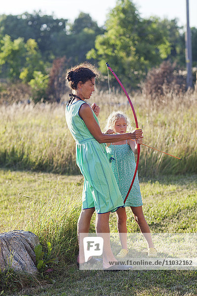 Mother and daughter playing with bow and arrow