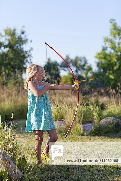 Girl playing with bow and arrow