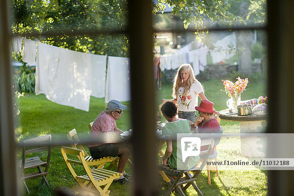 Family dining at outdoor table in garden seen from inside