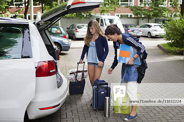 Mother and daughter packing luggage into car