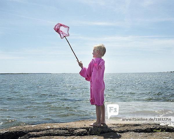 A boy in a bathrobe at the ocean