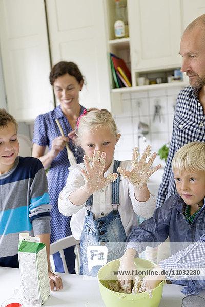 Family preparing food in kitchen