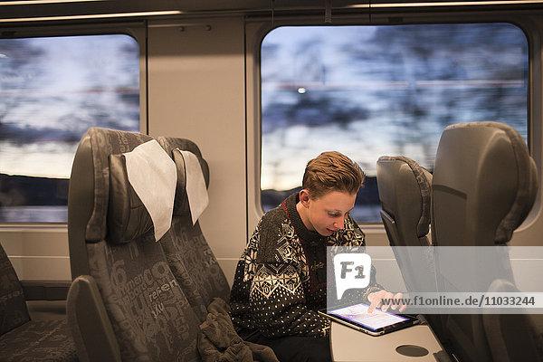 Teenage boy using tablet on train