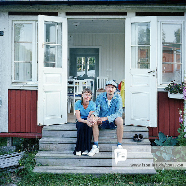 Mid adult couple sitting in front of house
