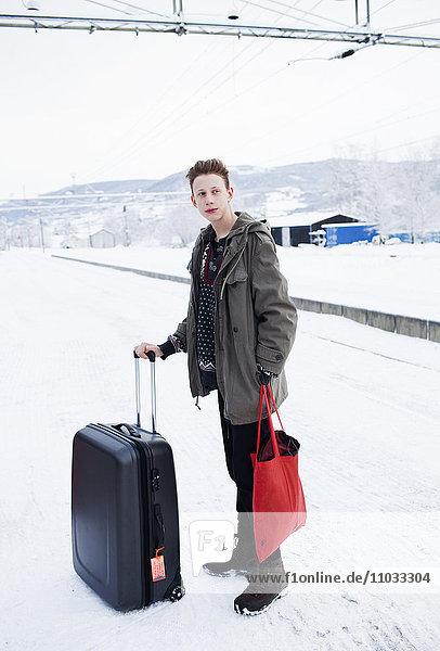 Teenage boy with suitcases on train platform