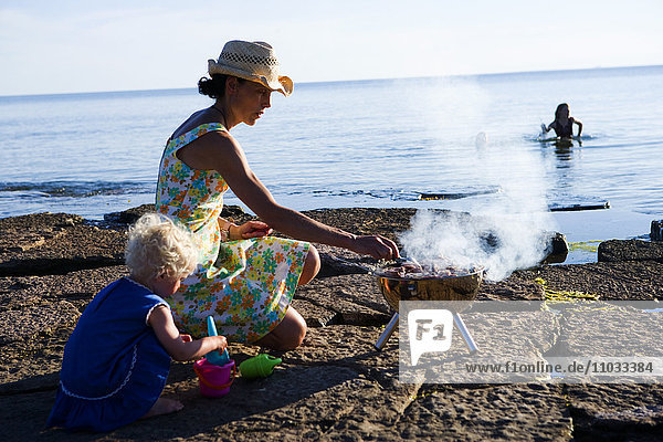 Mother barbecuing on a beach and chlidren swimming in the sea.