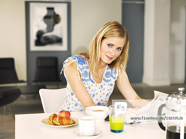 A woman reading the paper during breakfast.