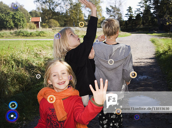 Three children playing with soap-bubbles.