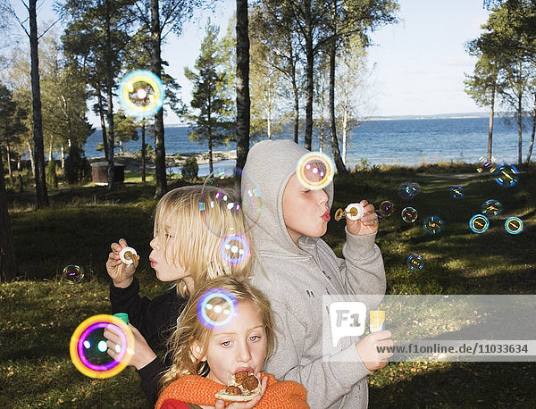 Three children with soap-bubbles.