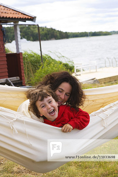 Mother and daugther playing in a hammock.