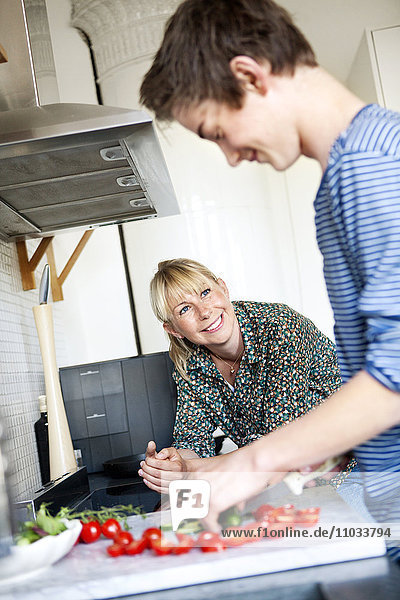 Teenage boy with mother in kitchen