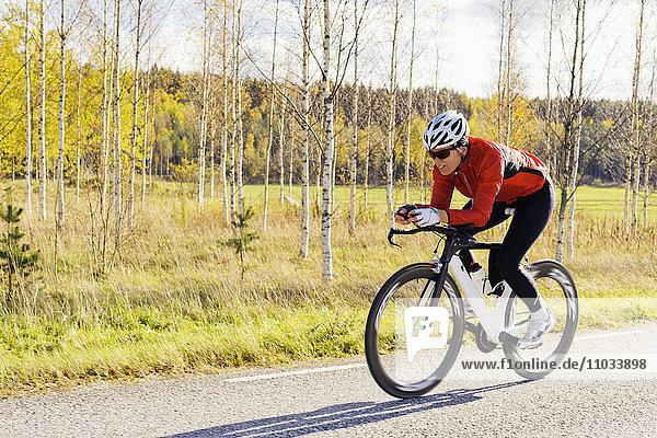 Woman riding bike down country road