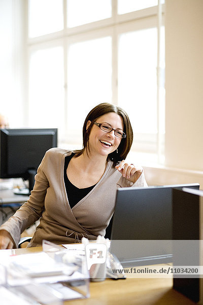 A laughing woman at her workplace.
