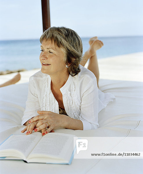 Woman lying on a bed and reading.