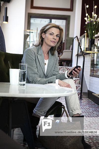 Businesswoman sitting in cafe with cell phone