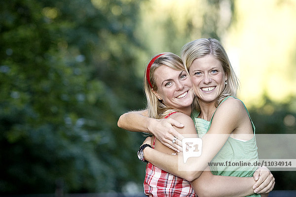 Two smiling women hugging  Sweden.