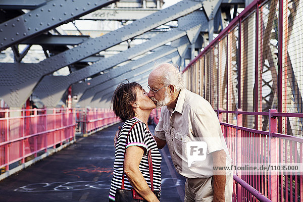 Senior couple kissing on bridge