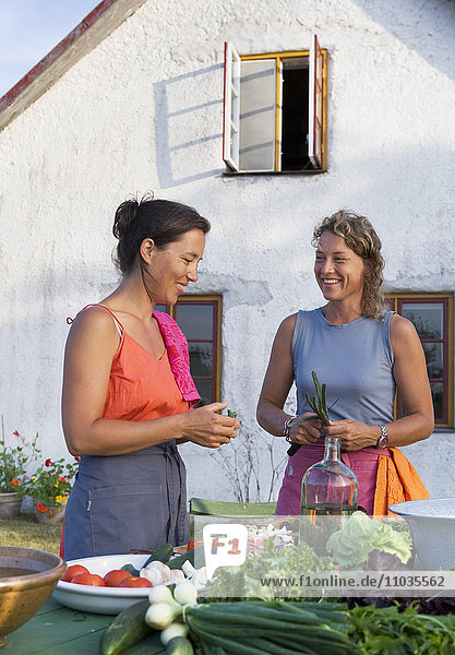 Two women preparing a meal outdoors.