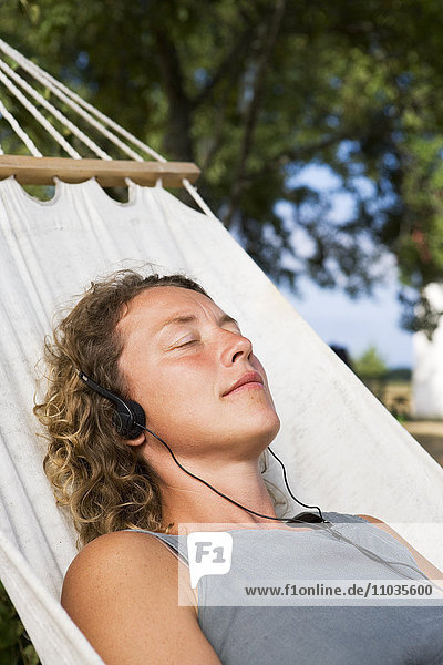 A woman with headphones resting in a hammock.