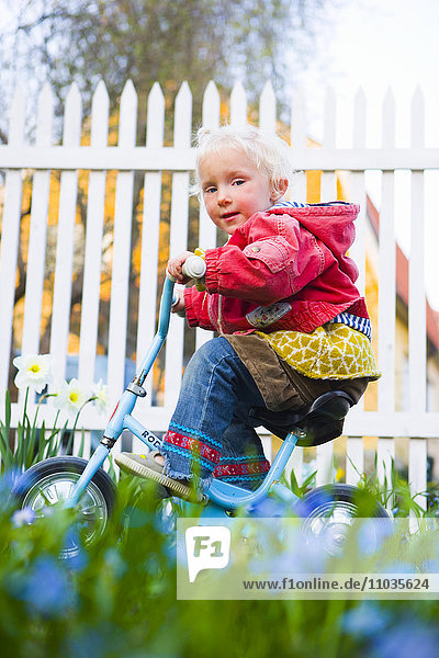 A small girl cycling.
