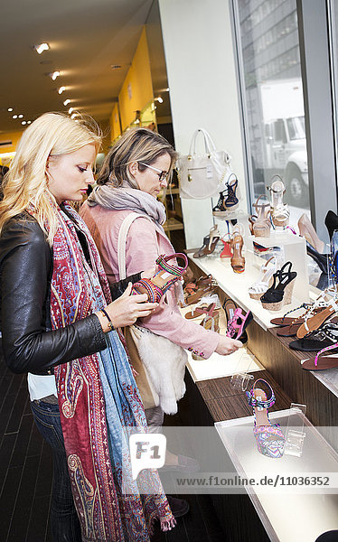 Mother and daughter watching shoes in shop