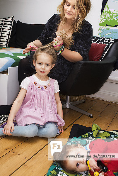 A mother doing her daughters hair  Sweden.