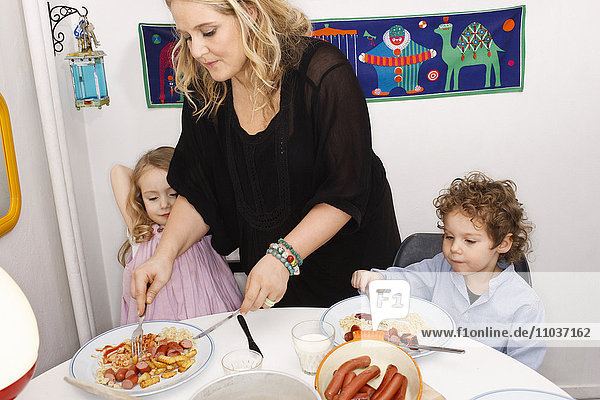 Mother helping her children at the dinner table  Sweden.