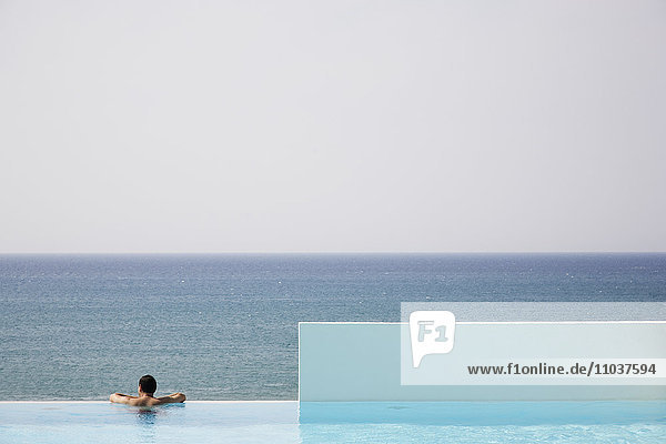 Man in a swimming-pool looking at the ocean  Greece.