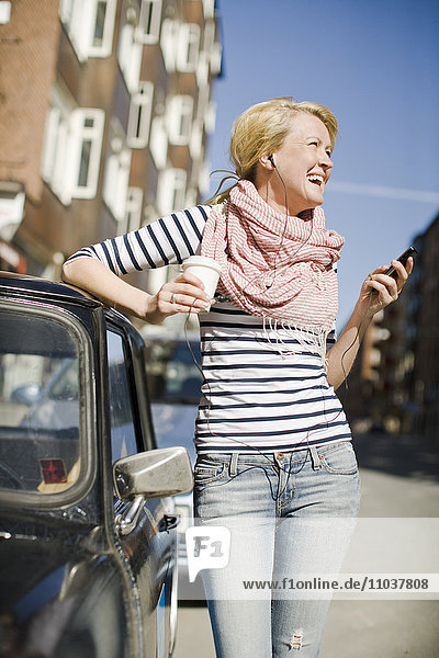 Woman using a mobile phone by a car  Sweden.