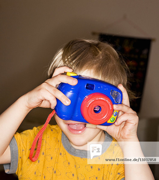 Boy taking photographs with a toy camera  Sweden.