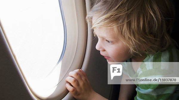 Boy looking out of an airplane window  Sweden. Boy looking out of an airplane window, Sweden.