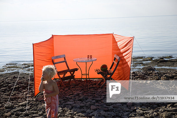 Chairs and a table behind a wind shield on a beach  Sweden.