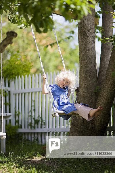Girl on a swing in a garden  Sweden.
