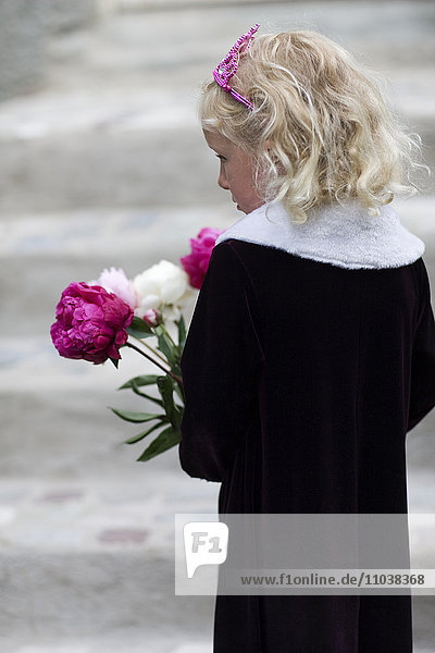 Girl in black holding a bouquet of peonies  Sweden.