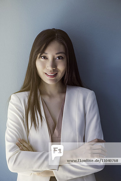 Businesswoman smiling with arms folded  portrait