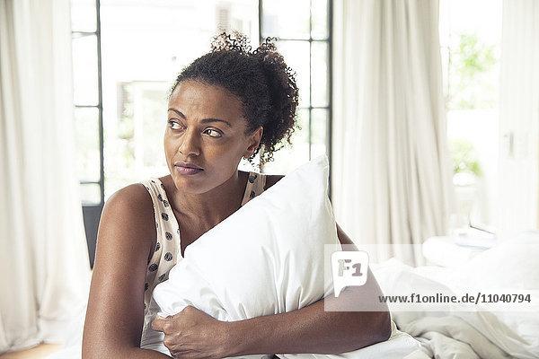 Frauenumarmungskissen auf dem Bett  Portrait