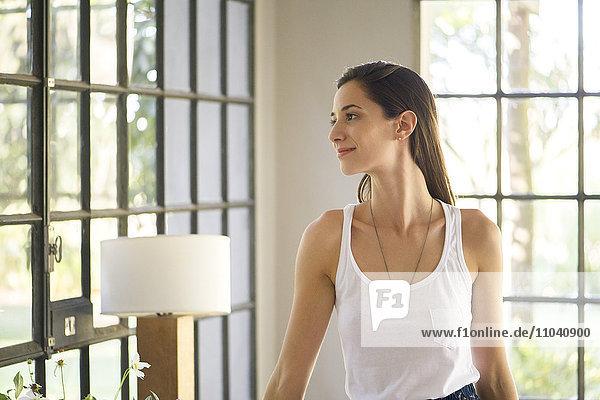 Frau genießt den Blick aus dem Wohnzimmerfenster