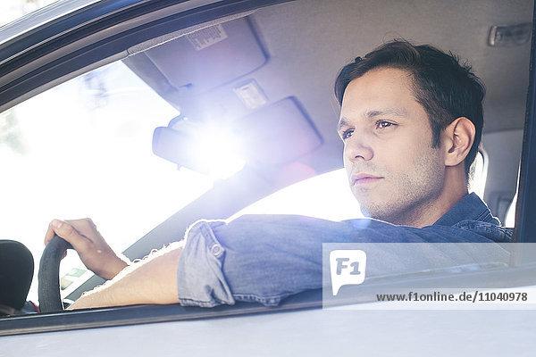 Mann genießt die Aussicht beim Autofahren